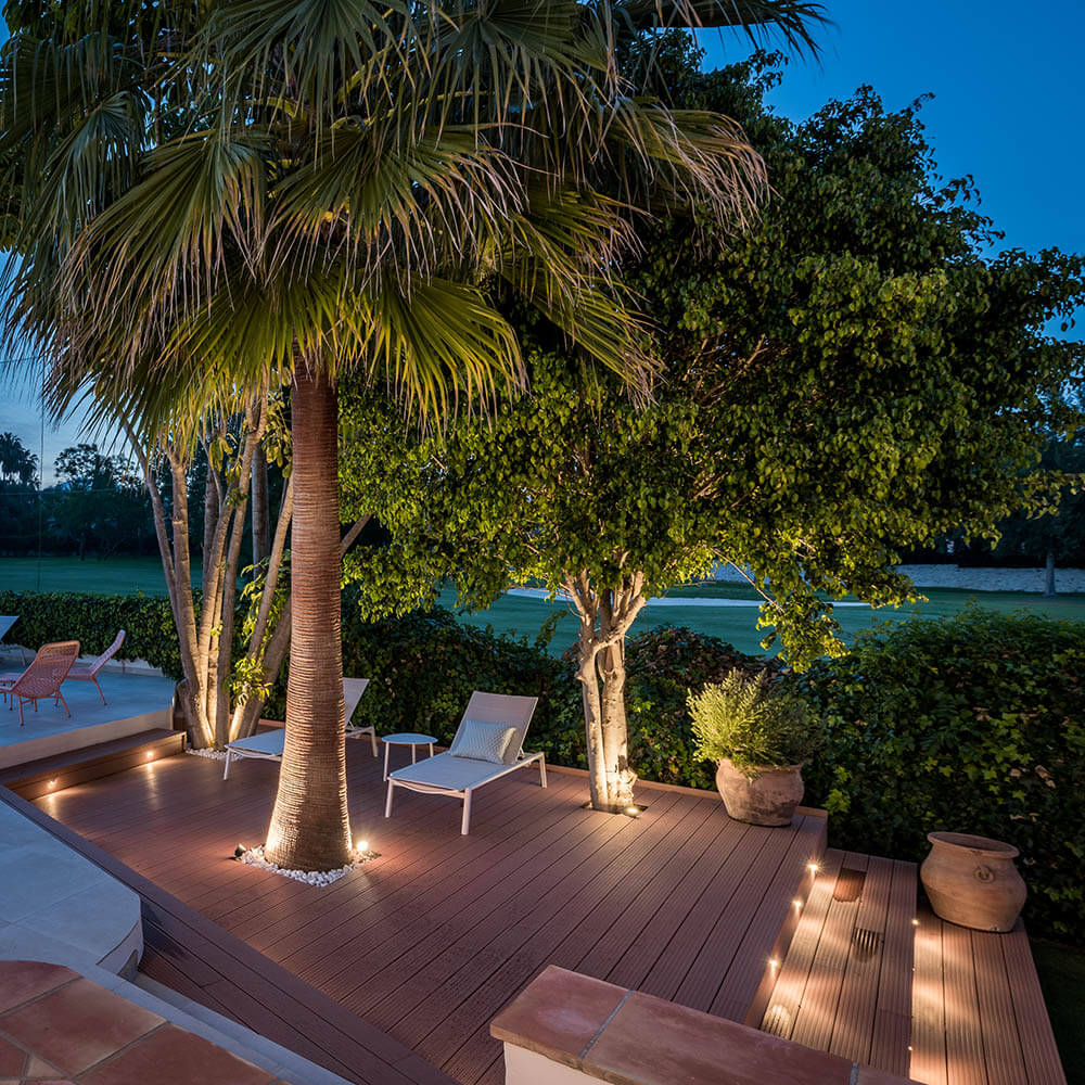 Accent lighting is used in this private spot to showcase the beautiful trees.