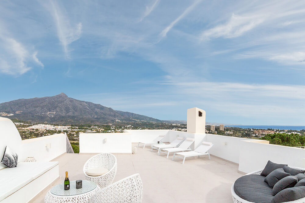 stylish spanish white rooftop chillout zone with mountain views