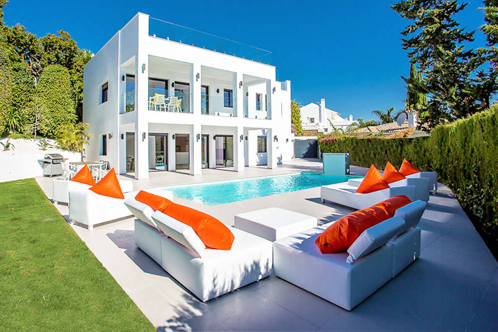 luxury modern white house with pool and sun couches spain