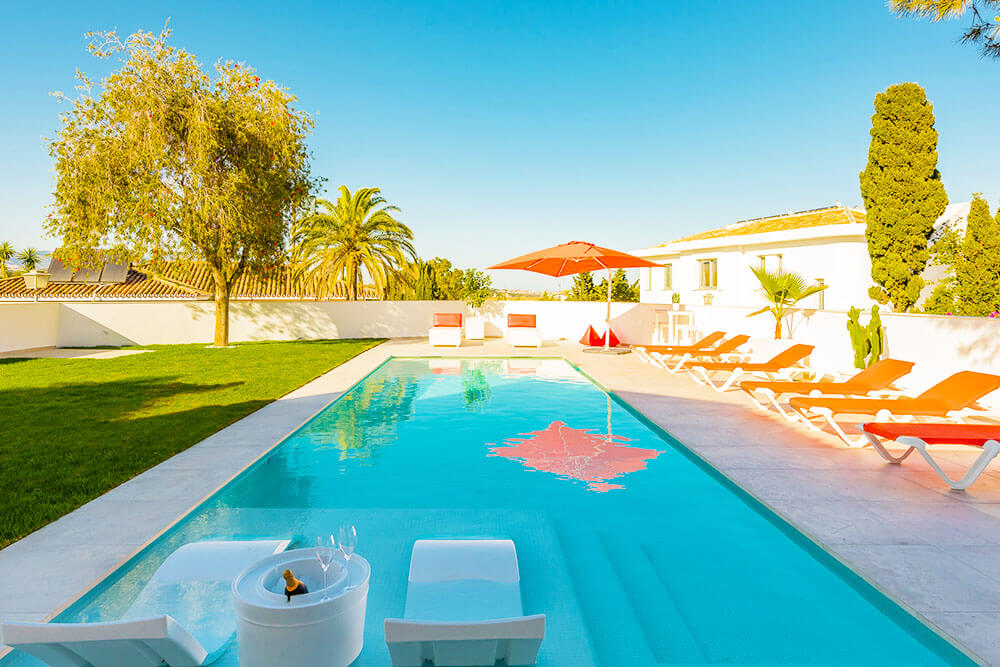 Classy pool seat and orange sun lounges in Marbella