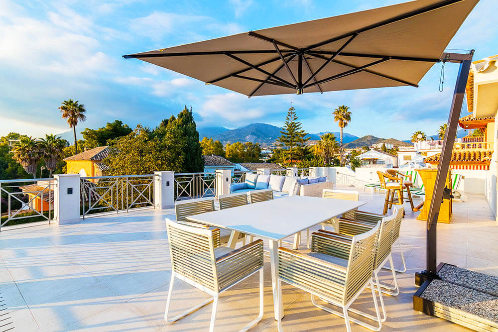 Stylish rooftop dinning in Marbella with sunshade and mountain views