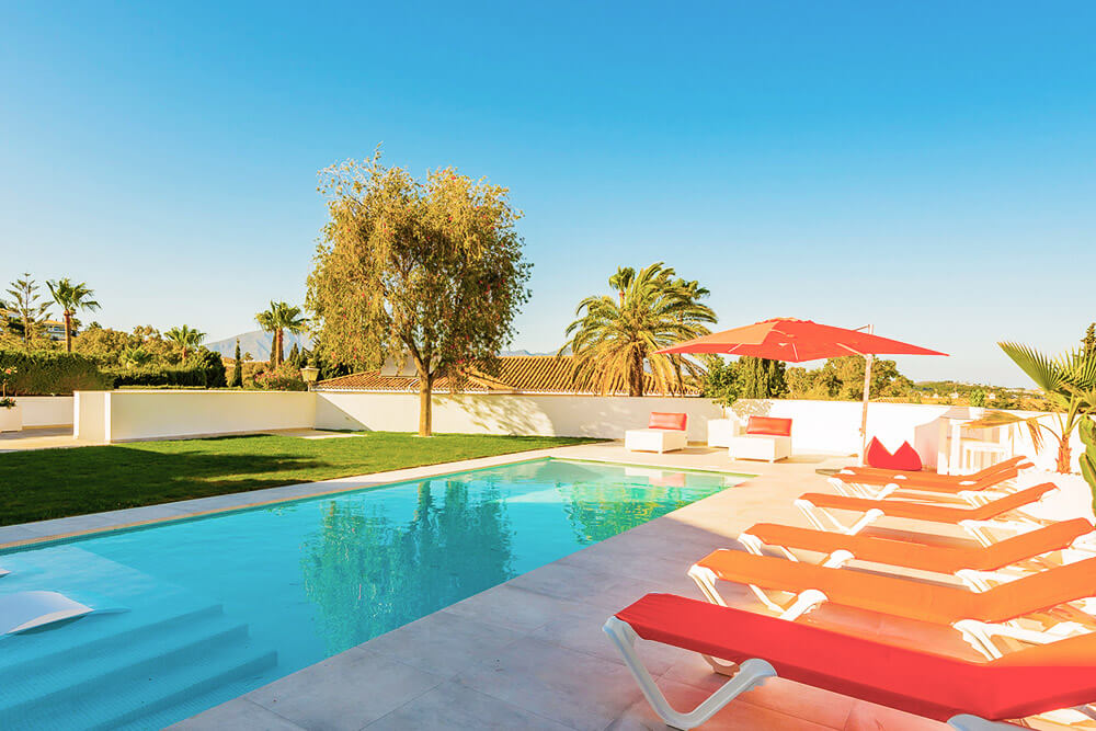 orange sunlounges by pool in costa del sol