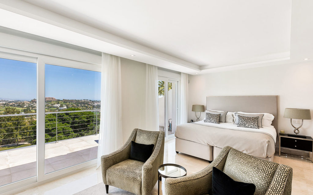Beautiful bedroom with lounge chairs, balcony and views in Marbella, Costa del Sol