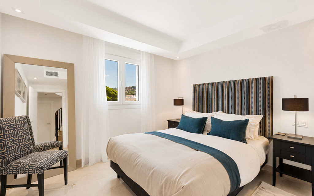 Classy bedroom with blue stripped bedhead in Costa del Sol