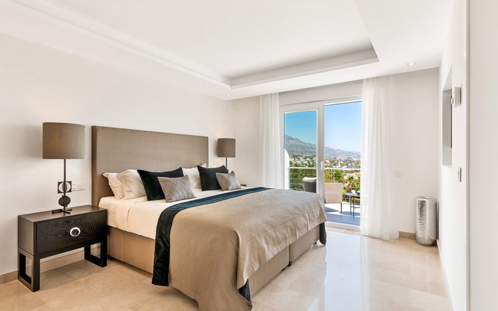 Beautiful bedroom with grey furnishings and dark timber with balcony overlooking mountains in Marbella