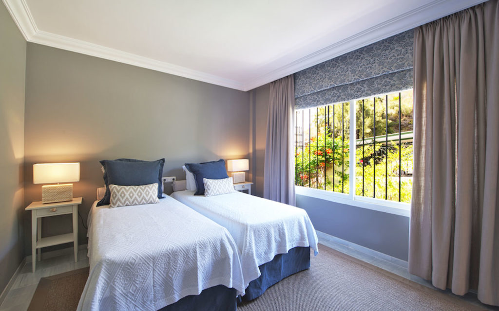 Classic style twin bedroom in Marbella with blue wall and details in Costa del Sol