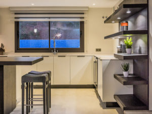 Modern kitchen with built in shelving and dark timber in Marbella