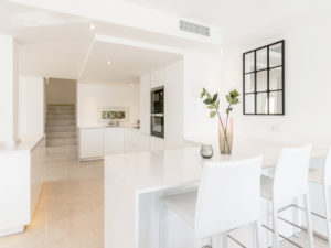 Beautiful modern white kitchen with barstools in Marbella