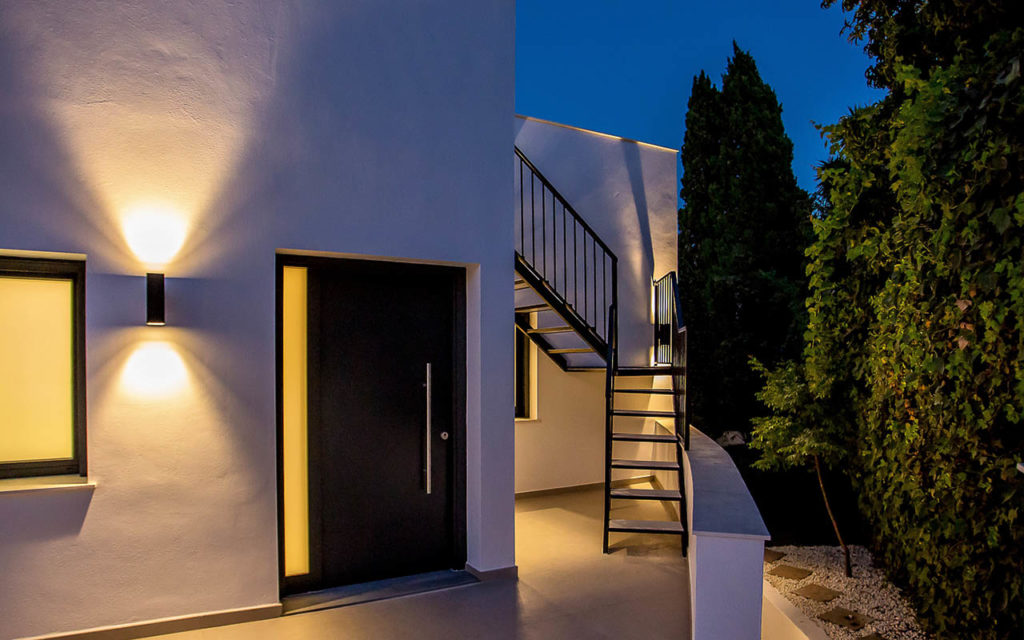 Modern entrance door to apartment in Marbella with night lighting