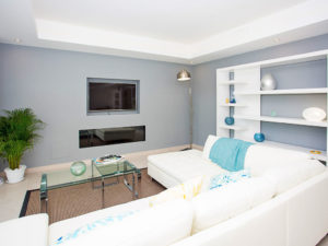 White couch with blue styling and grey wall