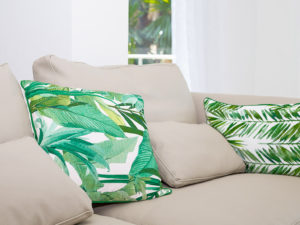 Beige couch with palm tree pillows