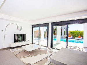modern white and metal living space opening to pool in Marbella