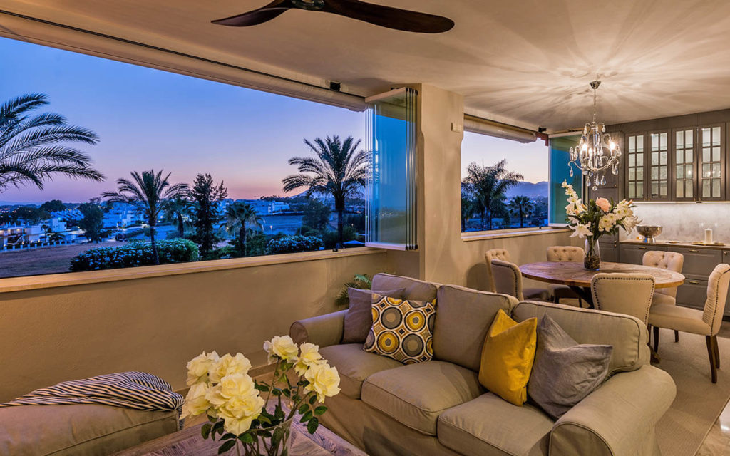 Contemporary living space bifold windows opening onto view of Puerto Banus, Costa del Sol