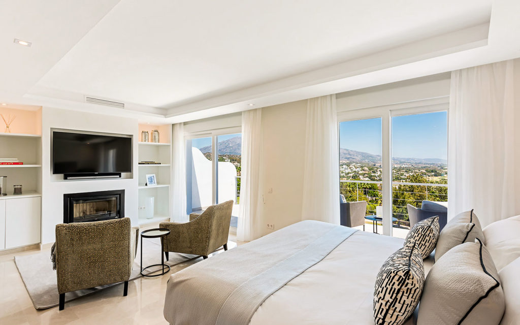 Stylish bedroom with built in fireplace overlooking mountains in La Quinta, Marbella