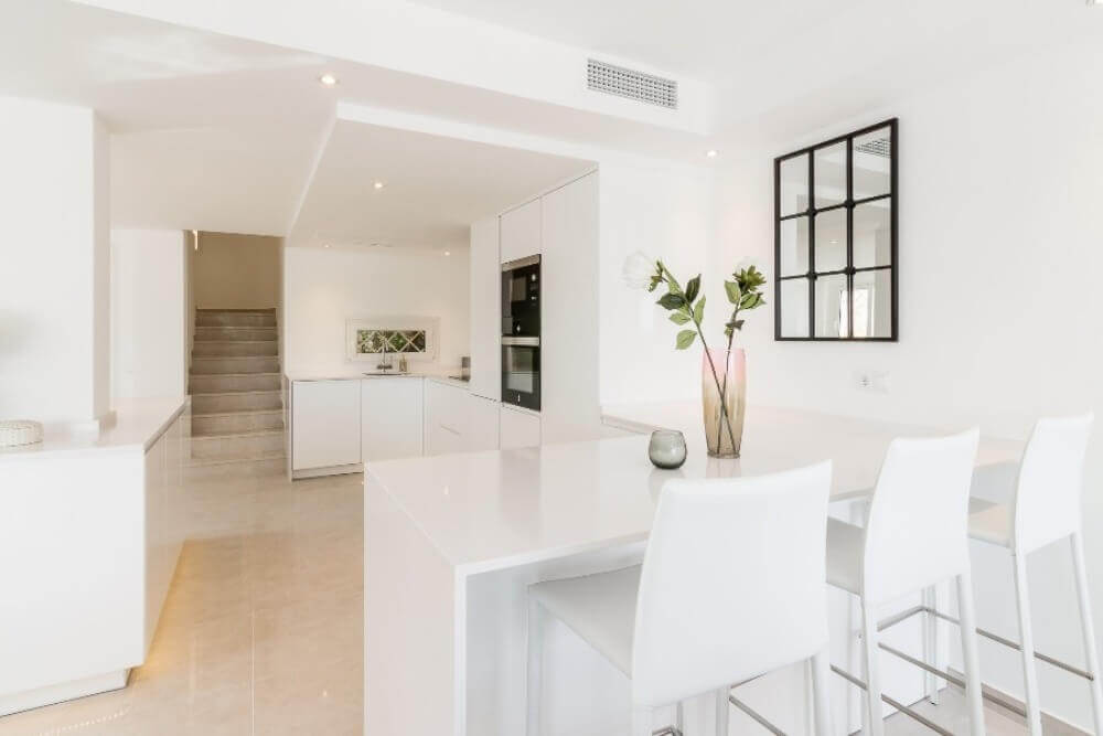 Stylish modern white kitchen with breakfast bar designed and built by ProMas in Marbella