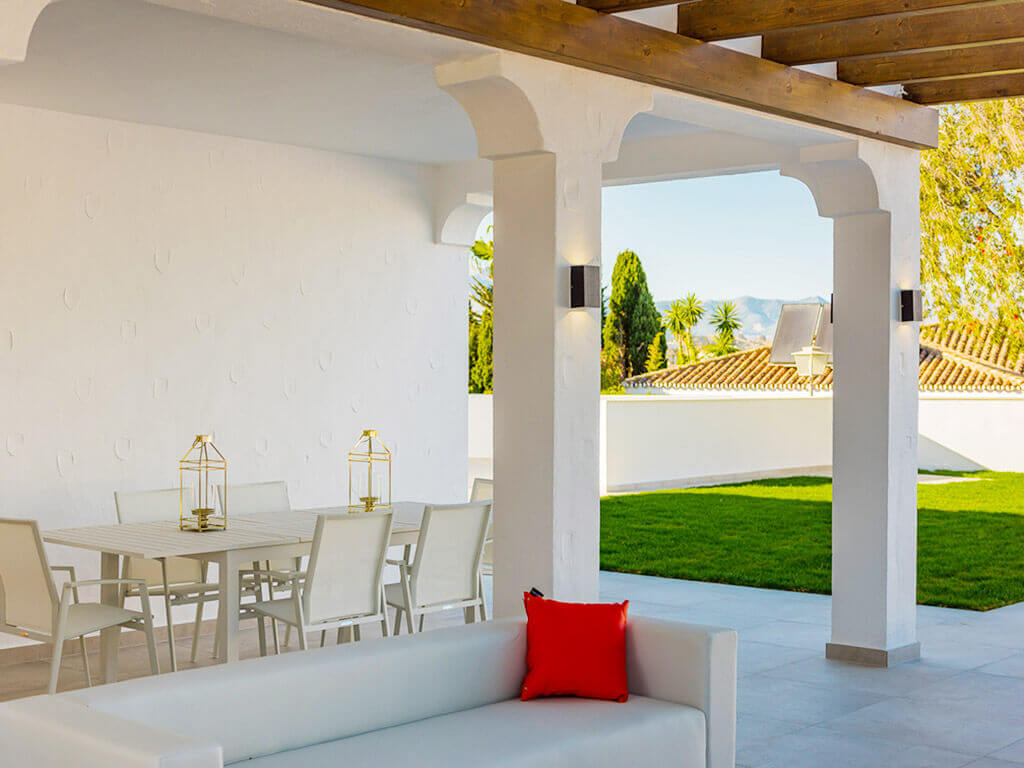 Stylish white outdoor living and dinning space with pergola looking to the mountains in Mijas Costa