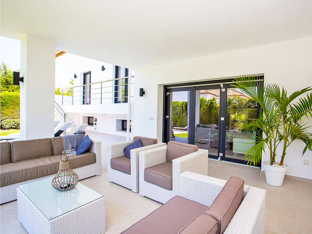 Stylish white and beige outdoor living area with blue trims