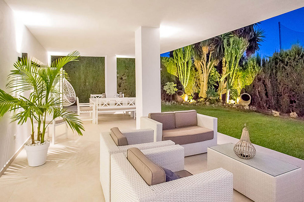 Stylish outdoor living area with Spanish garden and white furniture on the Costa del Sol