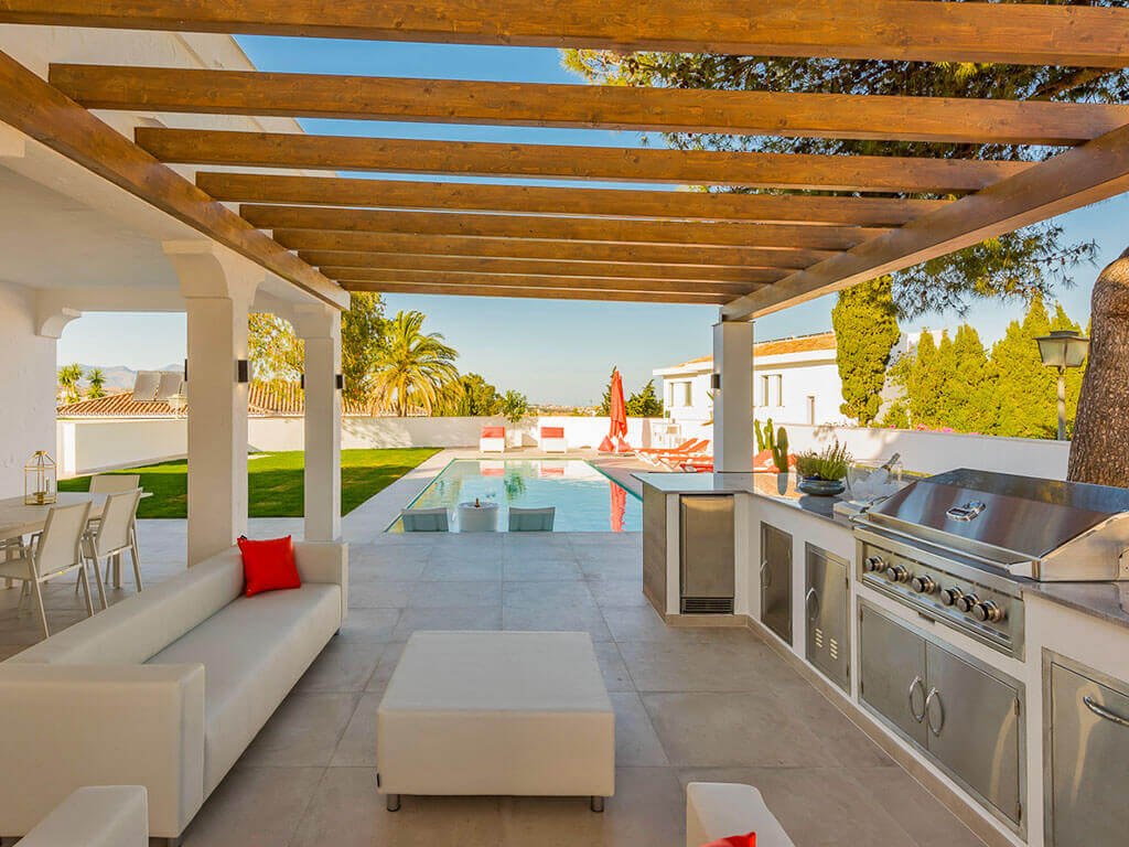 Modern outdoor kitchen and pool area with in pool chairs and designer white furniture