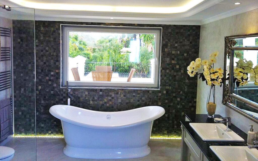 Standalone bath with black mosaic tiles