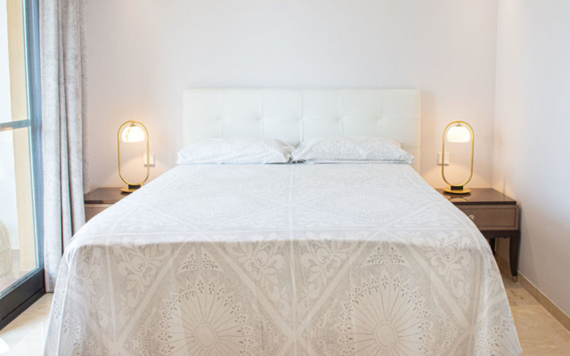 Stylish white bed and modern bedside tables and lamps