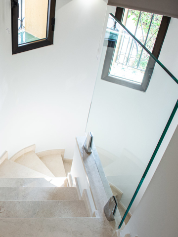 Stylish refurbished stairwell with marble stairs and glass divider