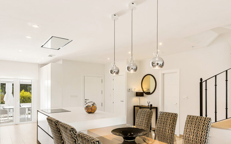 Layered lighting, downlights and pendants in an open plan kitchen